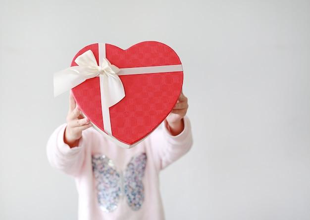 Adorable petite fille asiatique enfant montrant la boîte-cadeau coeur rouge sur fond blanc. kid donnant une boîte cadeau coeur rouge pour vous. concept de l'amour Photo Premium