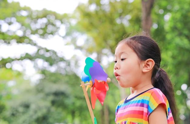 Adorable petite fille asiatique enfant soufflant une éolienne dans le jardin d'été. Photo Premium