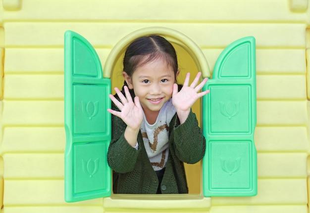 Adorable petite fille asiatique fille jouant avec la fenêtre playhouse jouet dans une aire de jeux Photo Premium
