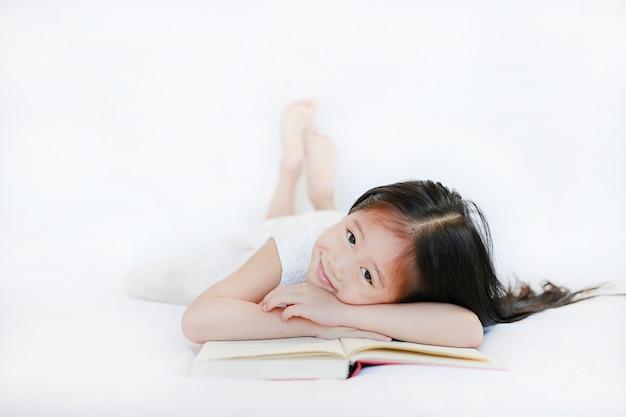 Adorable petite fille asiatique avec livre à couverture rigide, allongé sur le lit et regardant la caméra sur fond blanc. Photo Premium