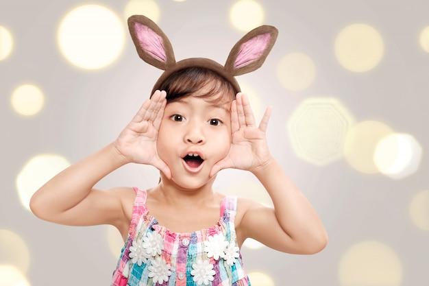 Adorable petite fille asiatique avec des oreilles de lapin en vacances de pâques Photo Premium