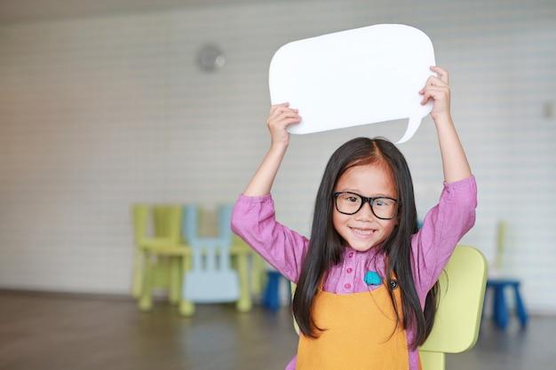 Adorable petite fille asiatique tenant une bulle de dialogue vide vide Photo Premium