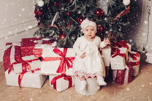 Adorable petite fille assise sur une boîte près de sapin de noël décorée d'ornements. coffrets cadeaux blancs avec des arcs rouges sous l'arbre. jolie enfant vêtue d'une robe blanche. effet de neige. Photo Premium