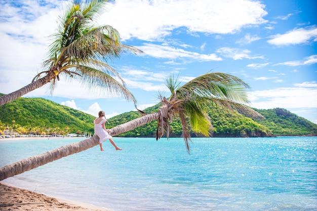Adorable petite fille assise sur un palmier pendant les vacances d'été sur la plage blanche Photo Premium