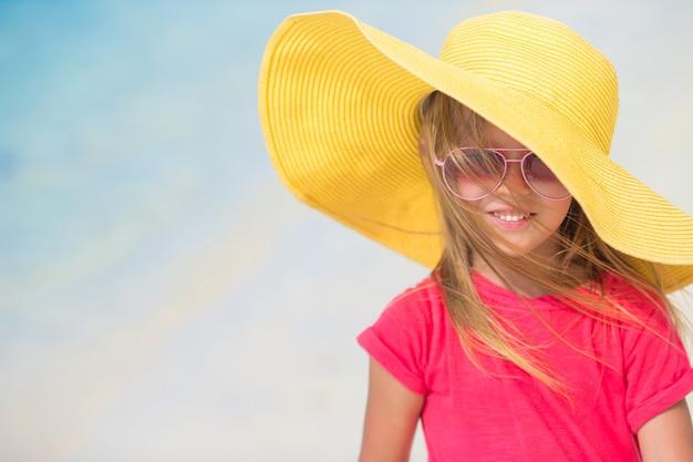 Adorable petite fille au chapeau sur la plage pendant les vacances d'été Photo Premium