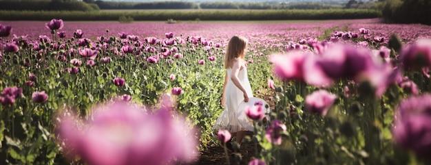 Adorable petite fille aux cheveux longs en robe blanche solitaire marchant dans le champ de lilas poppy flowers Photo Premium