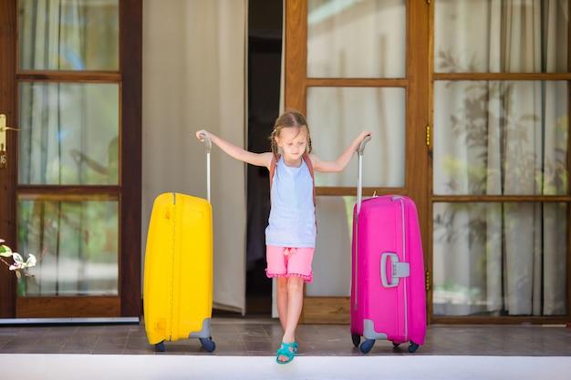 Adorable petite fille avec des bagages prêts à voyager Photo Premium