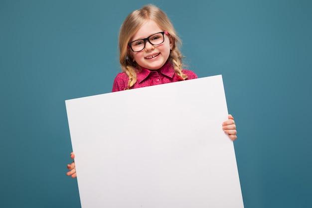 Adorable petite fille en chemise rose, pantalon noir et lunettes tient affiche vide Photo Premium