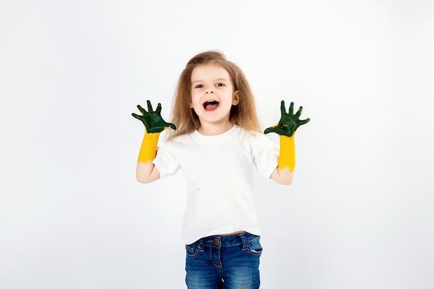 Adorable petite fille, coiffure moderne, chemise blanche, jeans, pose, hurlement, rugissement, sourire. elle a peint de la peinture sur ses mains. isolé. blanc. Photo Premium