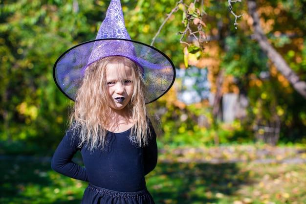 Adorable petite fille en costume de sorcière lance un sort à halloween Photo Premium