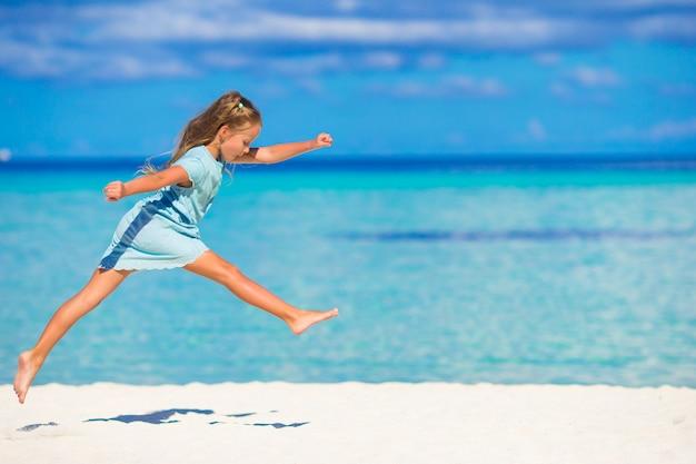 Adorable petite fille en cours d'exécution pendant les vacances à la plage Photo Premium