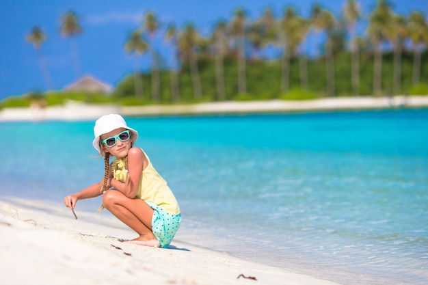 Adorable petite fille dessinant sur la plage blanche Photo Premium