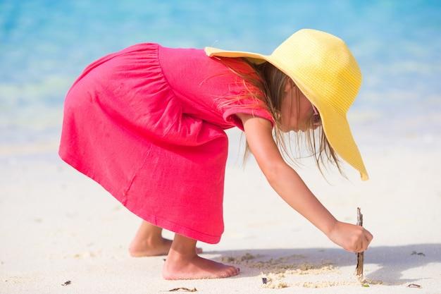 Adorable petite fille dessinant sur le sable blanc à la plage Photo Premium
