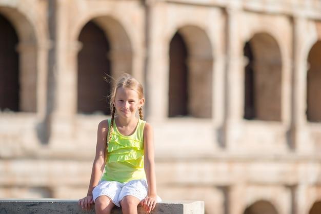 Adorable petite fille devant le colisée à rome, en italie. kid en vacances italiennes Photo Premium