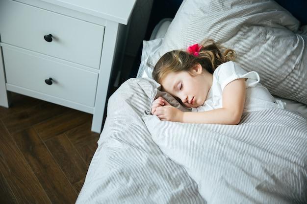 Adorable petite fille dormant dans son lit en pyjama sous la couverture chez elle, calme et paisible Photo Premium