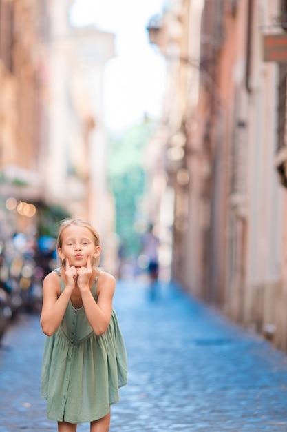 Adorable petite fille heureuse à l'extérieur dans une ville européenne. Photo Premium