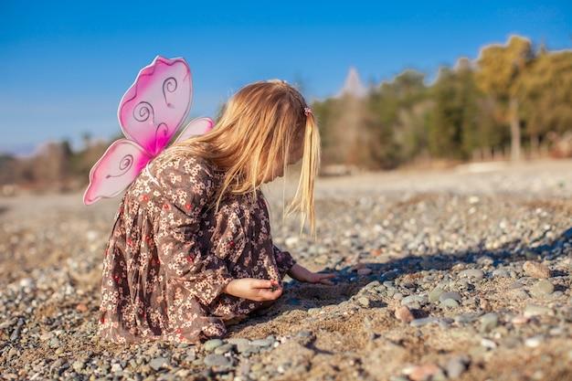 Adorable petite fille jouant sur la plage en une journée ensoleillée d'hiver Photo Premium