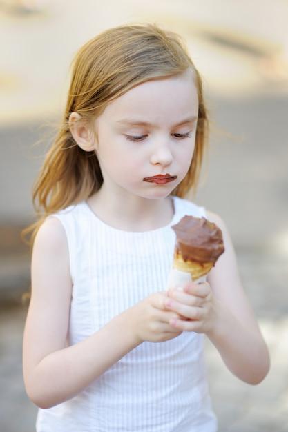 Adorable petite fille mangeant des glaces en plein air en été Photo Premium