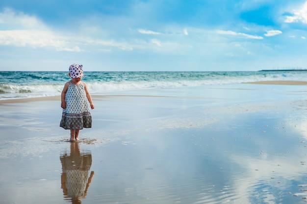 Adorable petite fille marchant sur le wateron la plage, mer méditerranée, espagne Photo Premium
