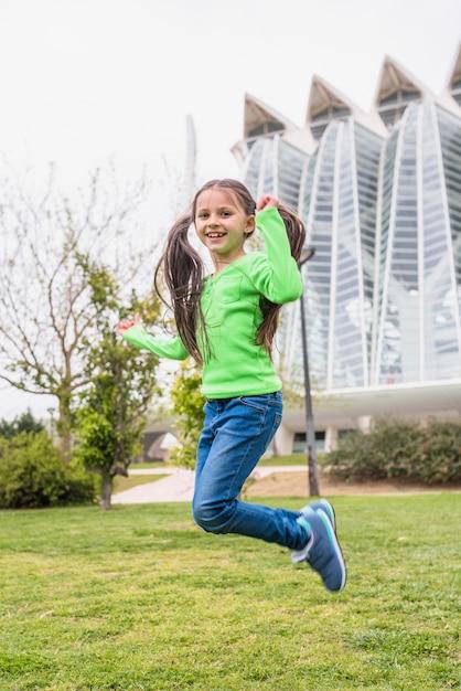 Adorable petite fille mignonne sautant sur l'herbe Photo gratuit
