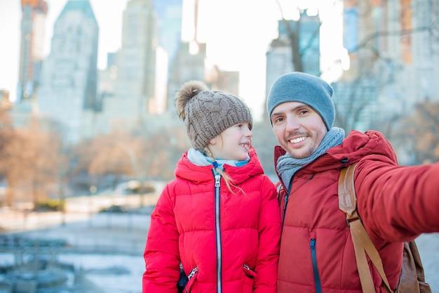 Adorable petite fille et papa s'amusent à central park à new york Photo Premium