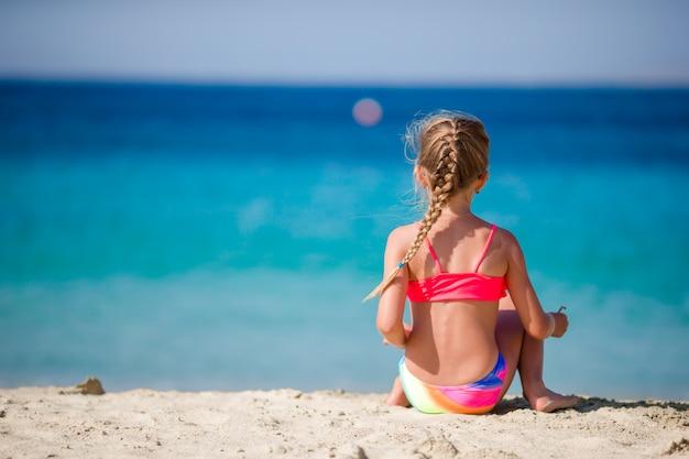 Adorable petite fille à la plage tropicale pendant les vacances Photo Premium