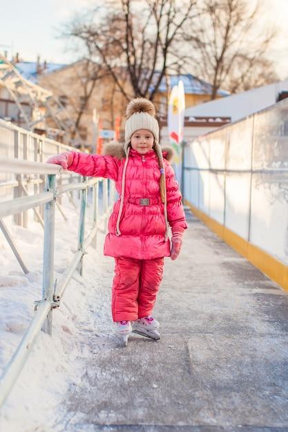 Adorable petite fille profitant du patinage à la patinoire Photo Premium