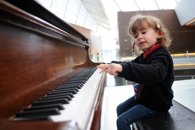 Adorable petite fille s'amusant à jouer du piano Photo gratuit
