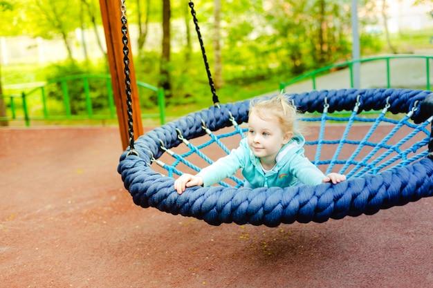 Adorable Petite Fille S'amuser Sur Une Balançoire En Corde Ronde Dans Une Aire De Jeux. Photo Premium
