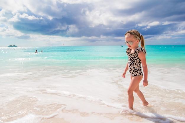 Adorable petite fille s'amuser à l'eau peu profonde sur la plage blanche Photo Premium