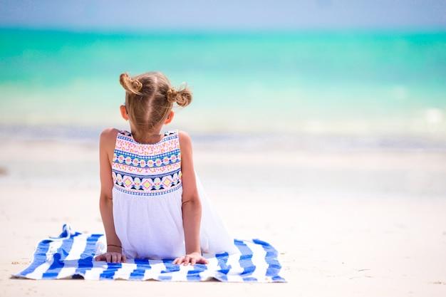 Adorable petite fille s'amuser à la plage tropicale pendant les vacances Photo Premium
