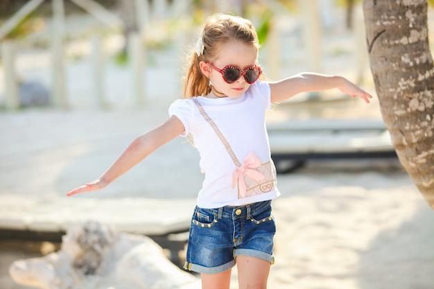 Adorable petite fille souriante heureuse sur les vacances à la plage se promène au bras droit Photo Premium