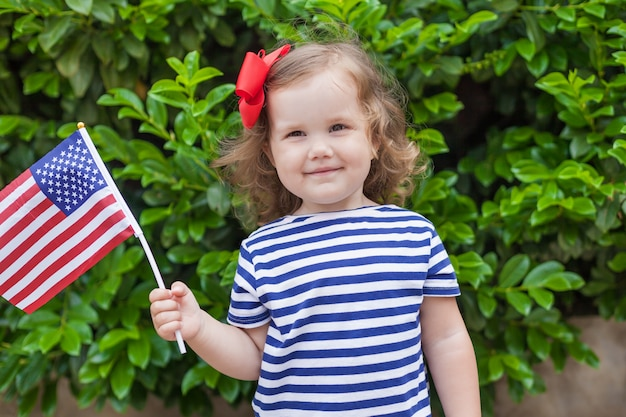 Adorable petite fille tenant un drapeau américain à l'extérieur sur une belle journée d'été Photo Premium