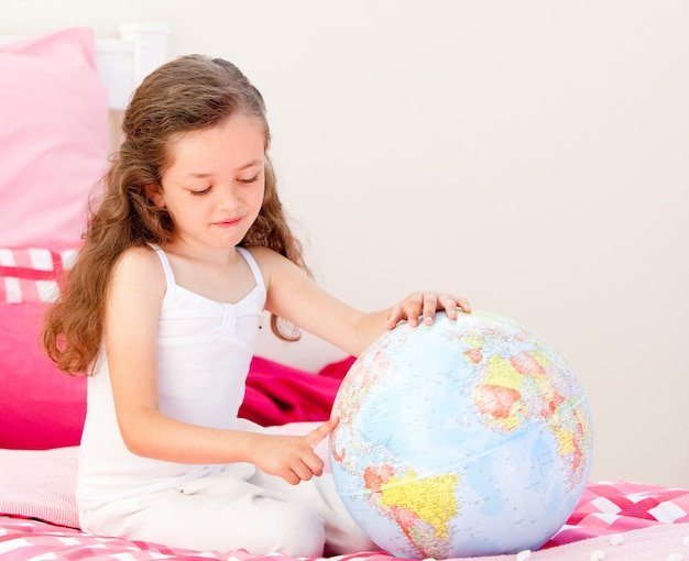 Adorable petite fille tenant un globe terrestre assis sur son lit Photo Premium