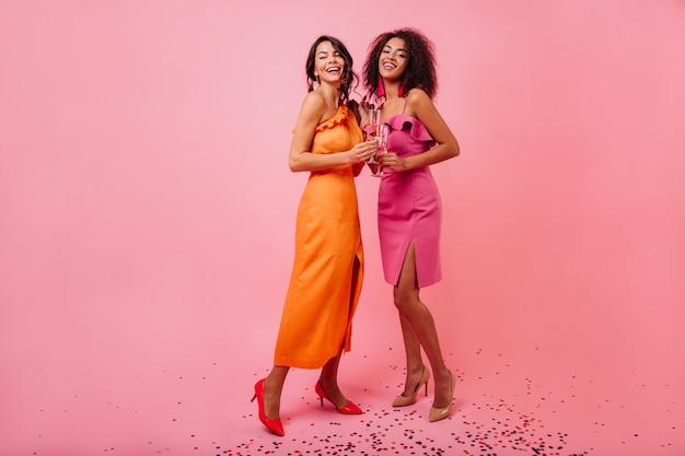 Adorables Femmes En Longue Robe Orange Profitant Du Tournage Photo gratuit