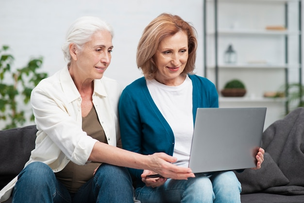 Adorables femmes matures utilisant un ordinateur portable Photo gratuit
