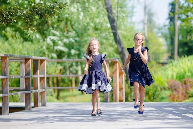 Adorables petites écolières à l'extérieur par une chaude journée de septembre. retour à l'école. Photo Premium