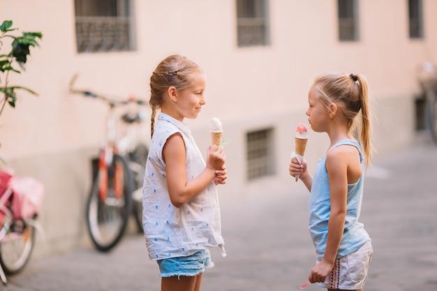 Adorables Petites Filles Mangeant Des Glaces à L'extérieur En été. Photo Premium