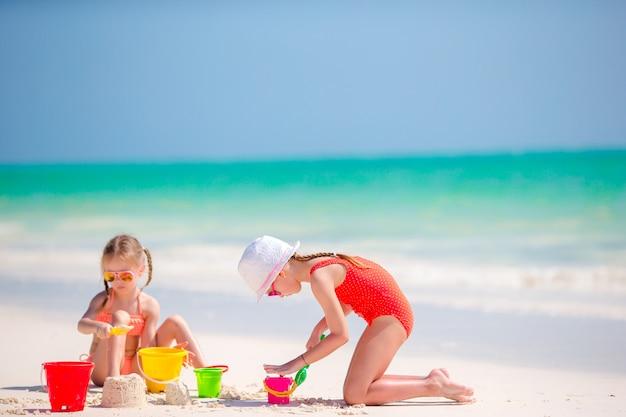 Adorables petites filles pendant les vacances d'été. enfants jouant avec des jouets de plage sur la plage blanche Photo Premium