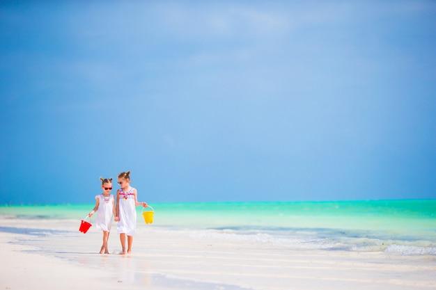 Adorables petites filles s'amusant sur la plage ensemble Photo Premium