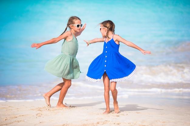 Les Adorables Petites Filles S'amusent Beaucoup Sur La Plage. Deux Beaux Enfants Sont Heureux Photo Premium