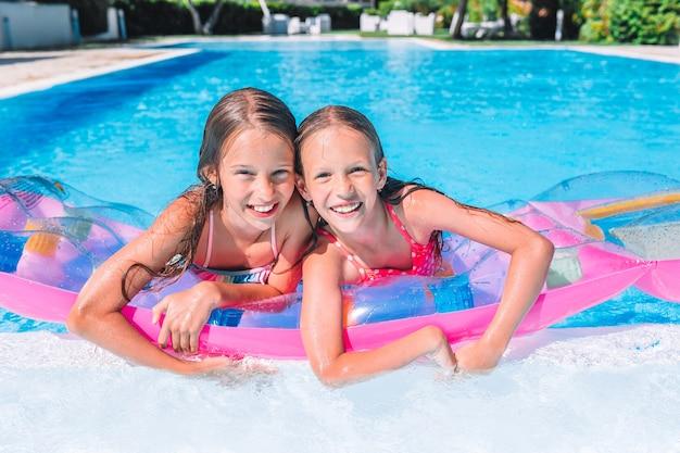 Adorables petites soeurs jouent dans la piscine extérieure Photo Premium