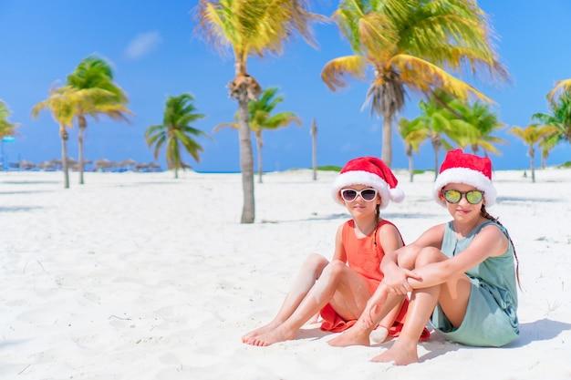 Adorables petits enfants au bonnet de noel pendant les vacances de noël à la plage. nouvel an sur la plage Photo Premium