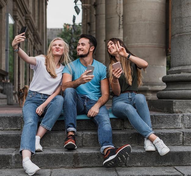 Ados Assis Dans Les Escaliers Et Prenant Un Selfie Photo gratuit