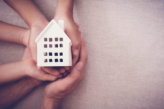 Adulte et enfant mains tenant concept maison blanche, maison familiale et sans abri Photo Premium