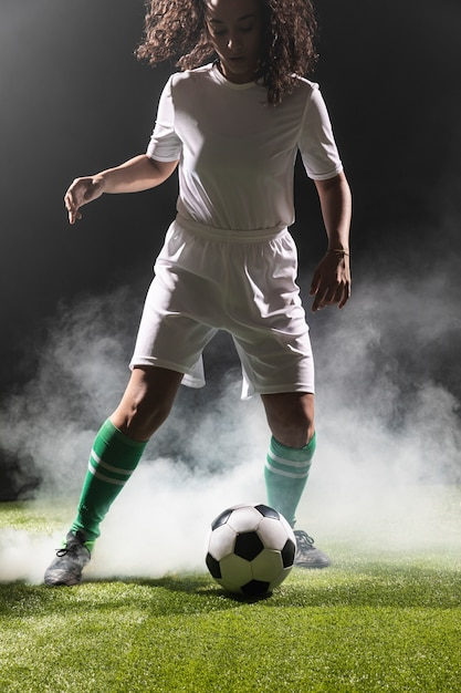 Adulte fit femme jouant au football Photo gratuit