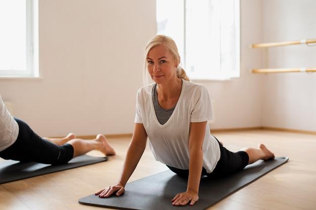 Adulte fit femme pratiquant le yoga Photo gratuit