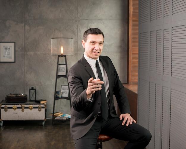 Adulte heureux homme d'affaires pointant à la caméra Photo gratuit