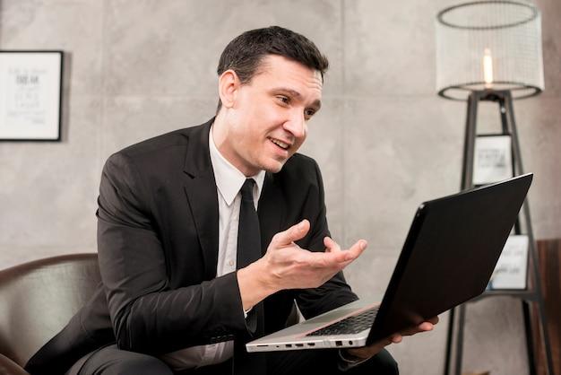Adulte, souriant, homme affaires, navigation, ordinateur portable, chez soi Photo gratuit