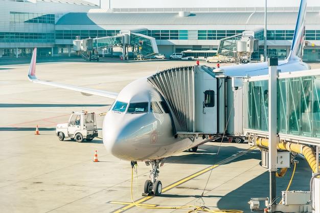 Aéronef avec tunnel de passage en préparation pour le départ d'un aéroport. Photo Premium